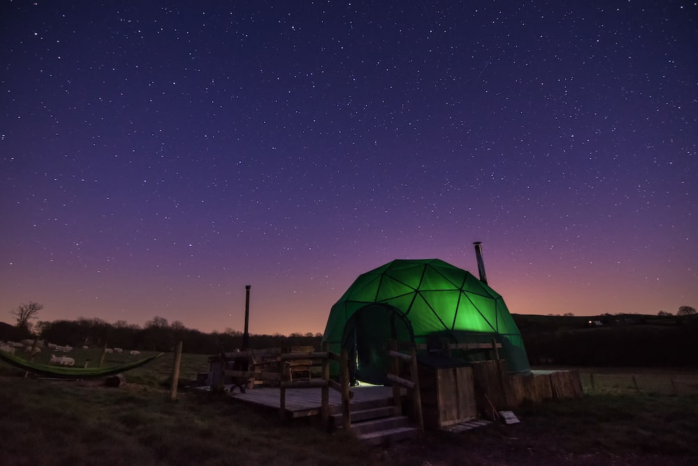 glowing-green-geodome-glamping-at-night-under-the-stars-beech-dome-cosy-under-canvas-kington-powys