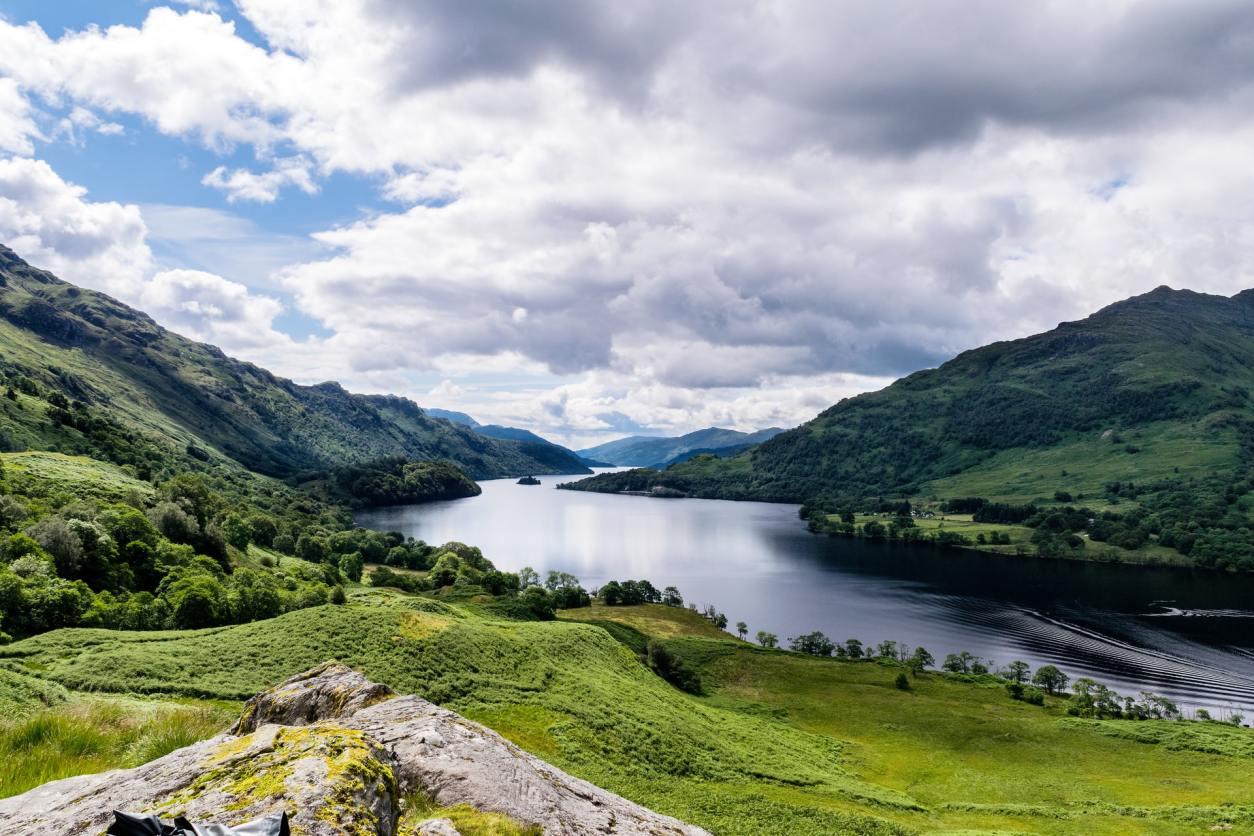 green-grass-field-near-lake-amid-mountains-under-cloudy-sky-loch-lomond-scenic-drives-in-scotland