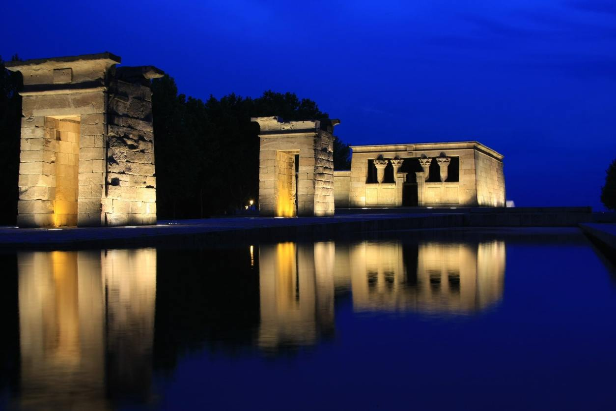 old-temple-lit-up-by-lights-at-night-and-reflected-in-pond-temple-of-debod