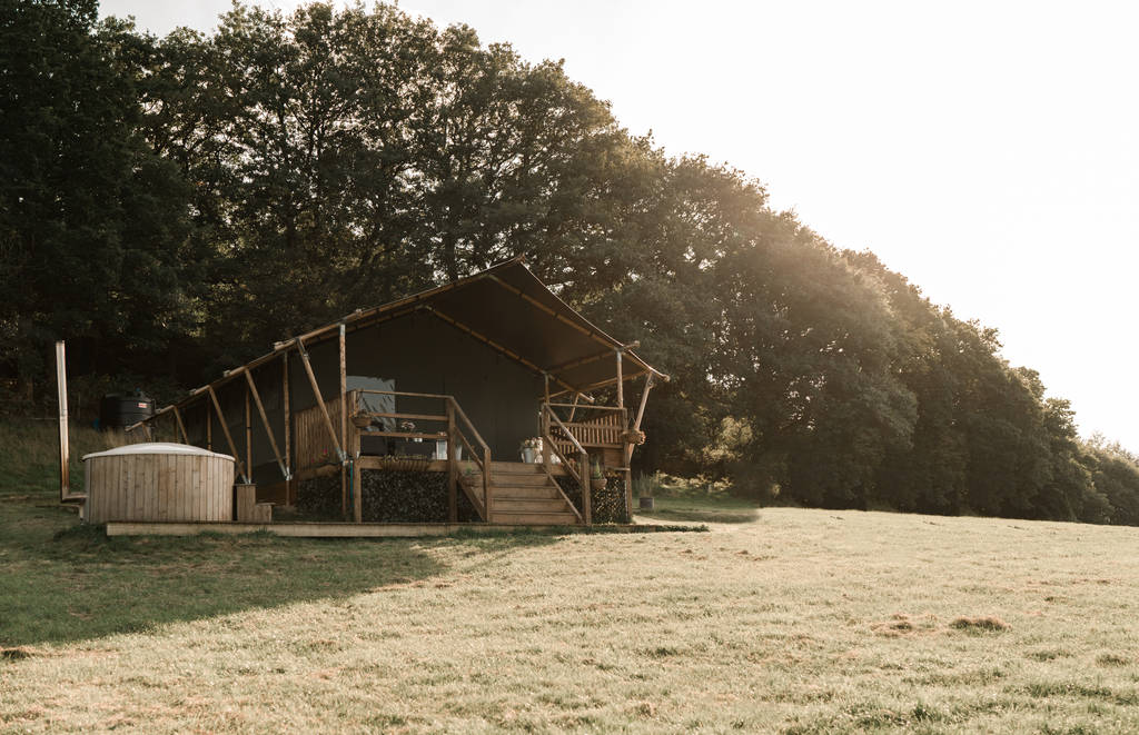 safari-tent-and-hot-tub-in-field-in-front-of-trees-two-valleys-retreat-safari-tent-presteigne-powys