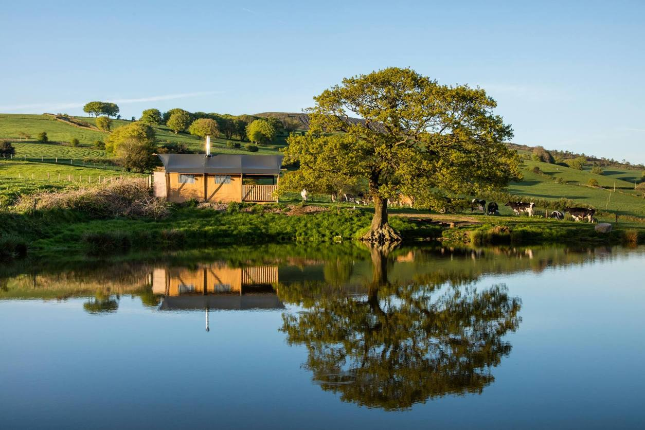 safari-tent-by-lake-in-front-of-tree-with-hills-in-the-background-under-the-oak-safari-tents-in-caerphilly-glamping-with-hot-tub-wales