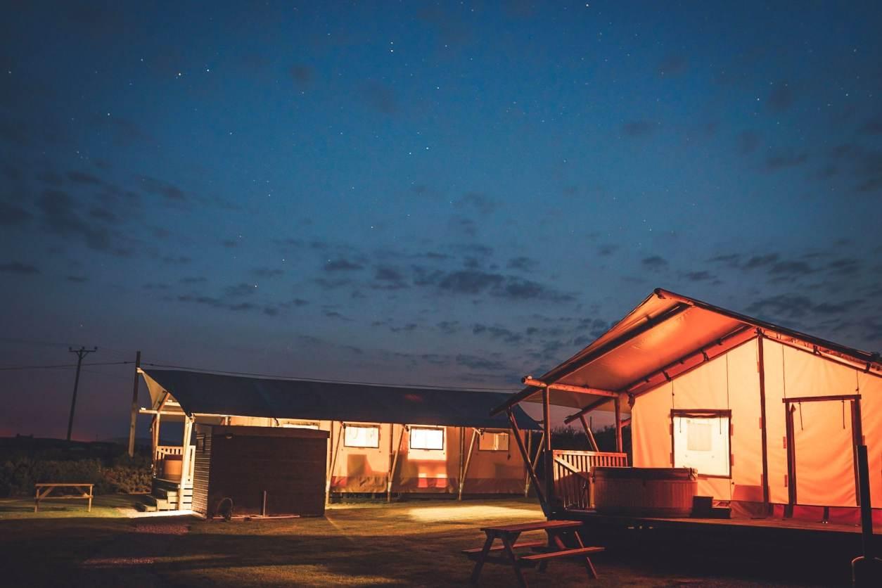 safari-tents-lit-up-orange-at-night-under-the-stars-at-night-nightsky-glamping-pwllheli,-gwynedd-glamping-with-hot-tub-wales