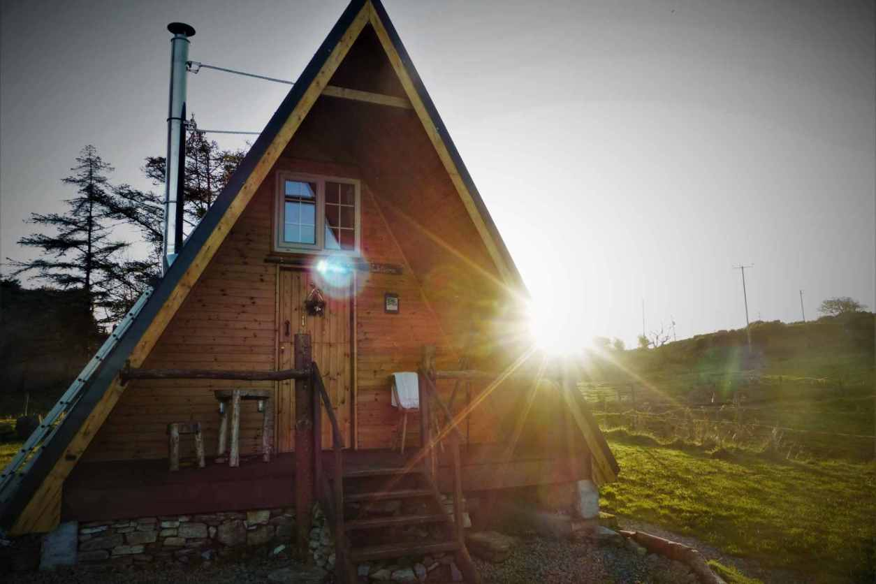 a-framed-cabin-tom-creans-eco-cabin-in-field-at-sunset