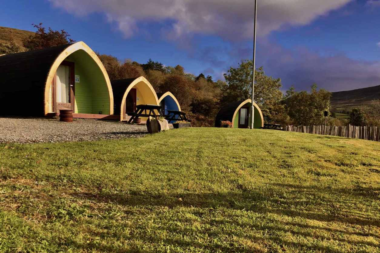 colourful-glamping-pods-with-picnic-tables-in-field-east-coast-adventure-pods