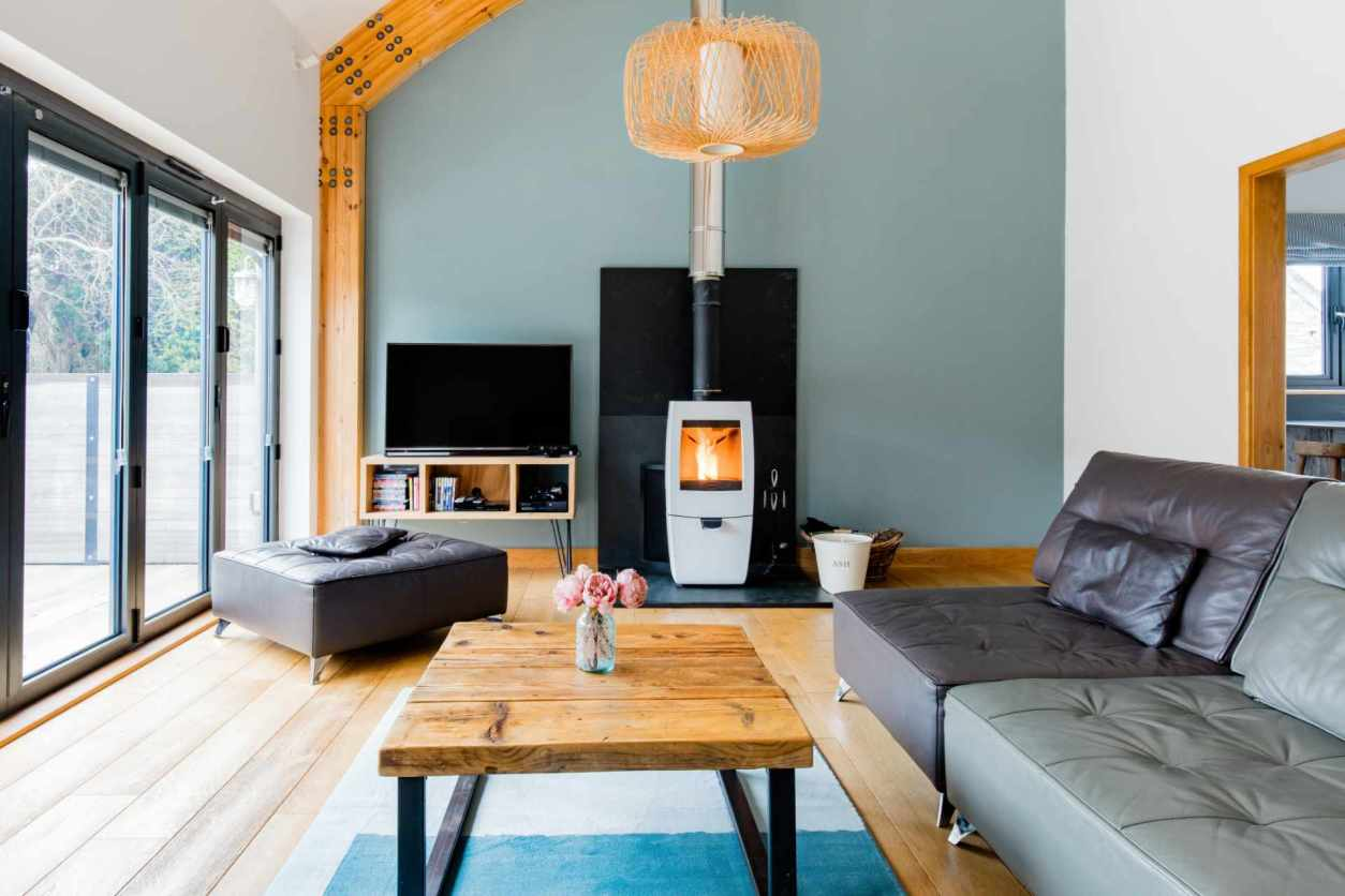 cosy-living-room-with-sofas-and-log-burner-in-barn-holiday-home-in-bude