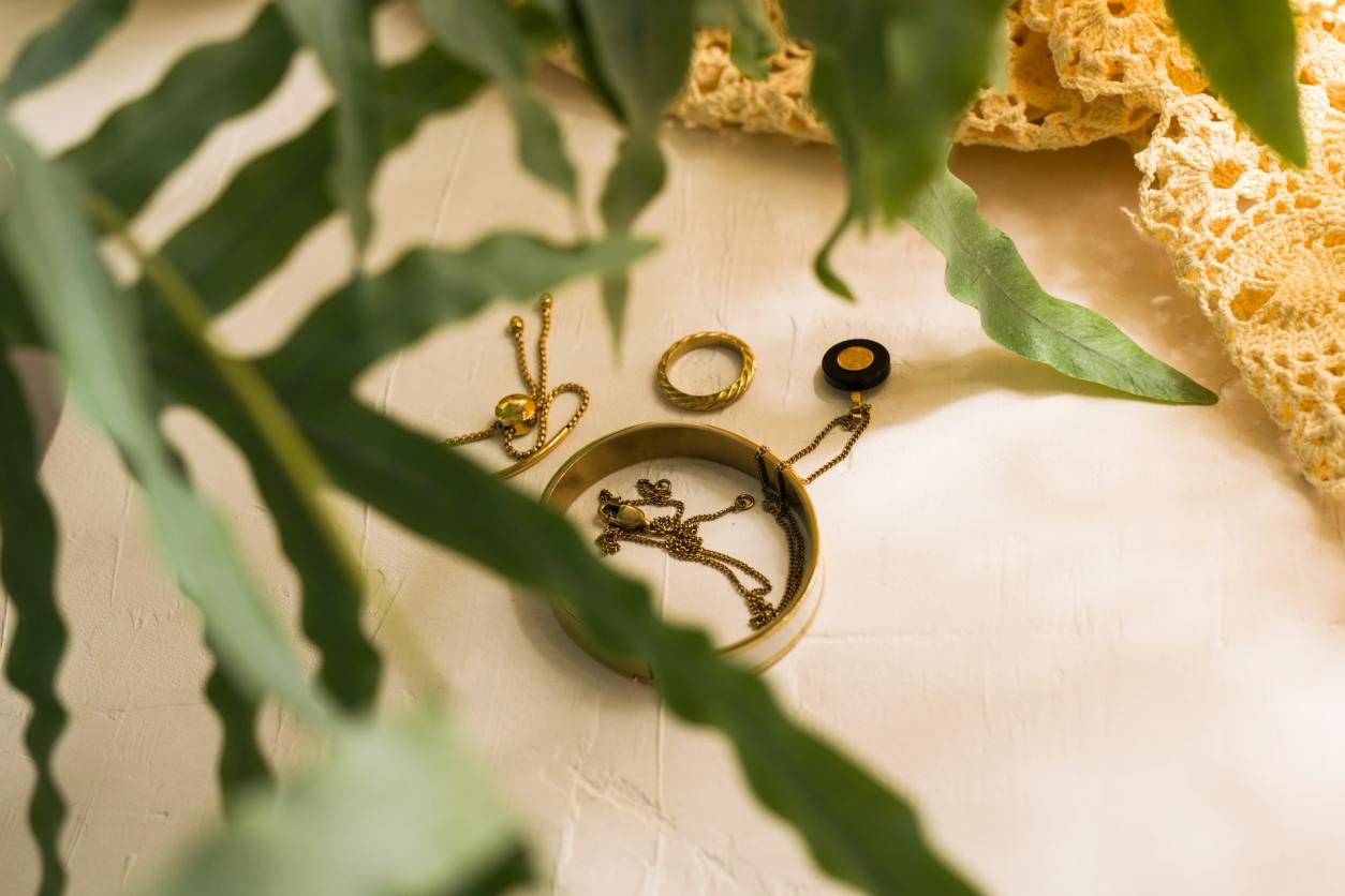 gold-jewellery-on-white-surface-behind-plant-leaves