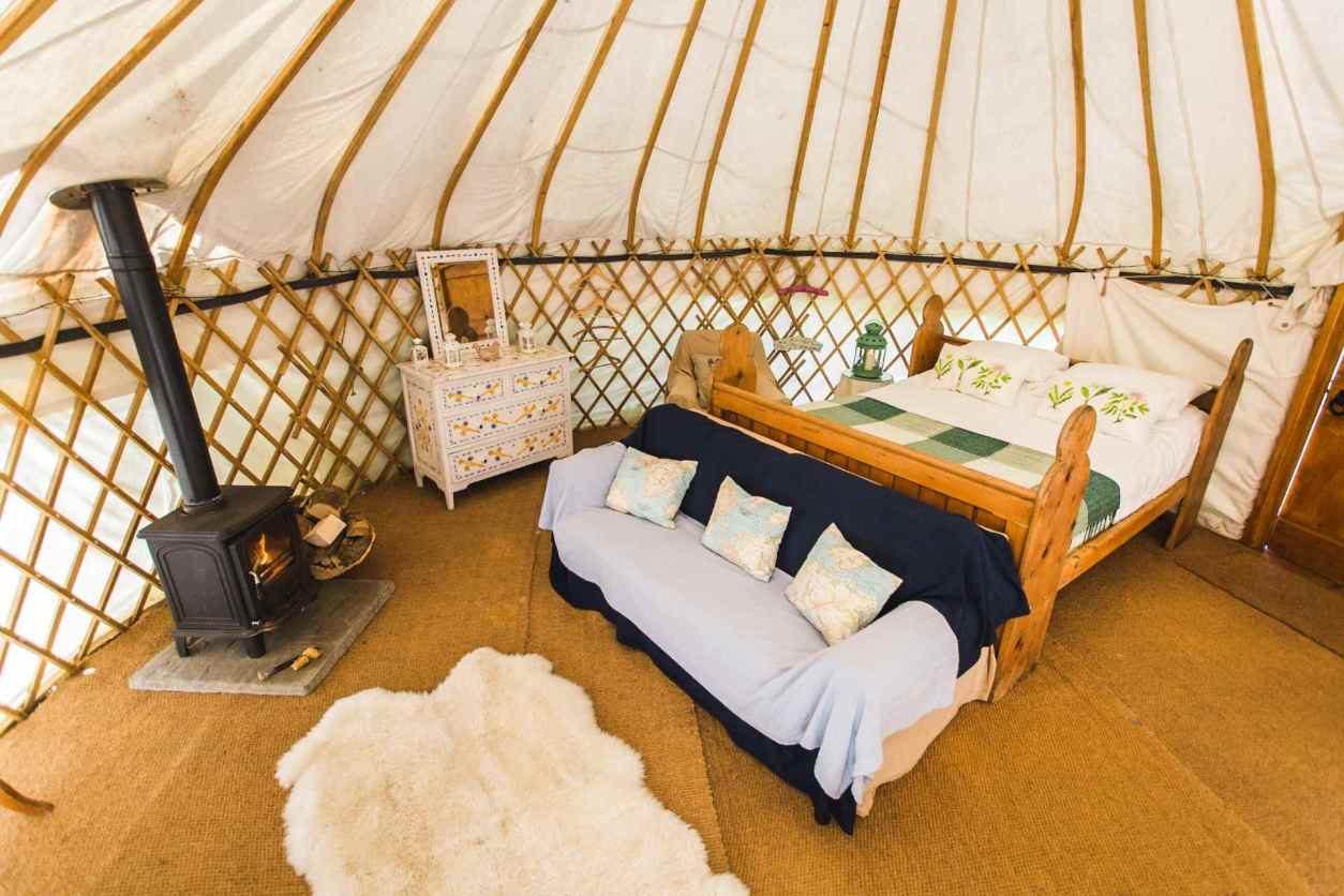 interior-of-rock-farm-slane-yurt-with-double-bed-and-sofa-glamping-with-hot-tub-ireland