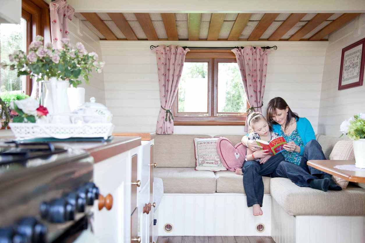 mother-and-daughter-sat-on-sofa-reading-in-tepee-valley-campsite-gypsy-caravan