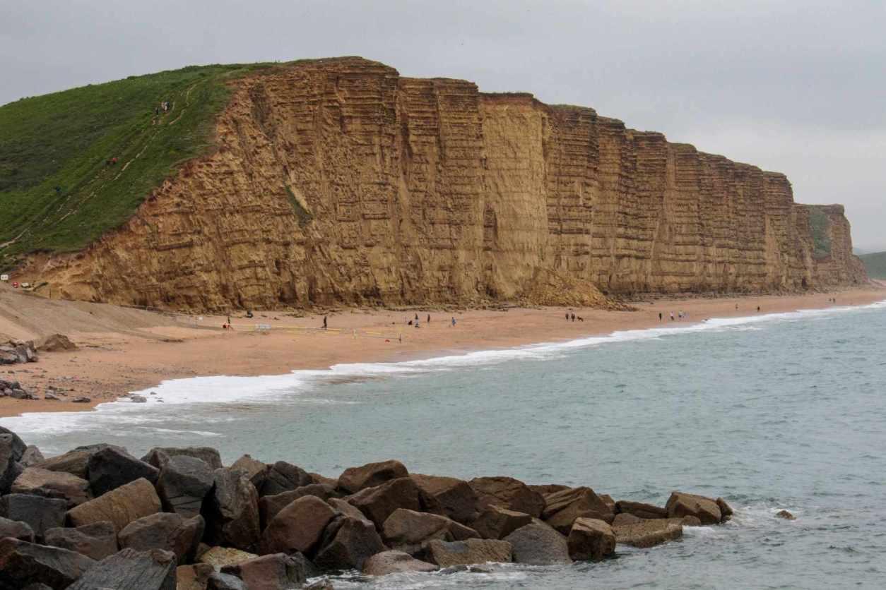 people-walking-along-sandy-beach-by-cliffs-west-bay