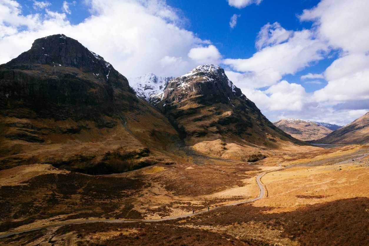 road-going-through-glencoe-with-mountains-on-either-side-day-trips-from-glasgow