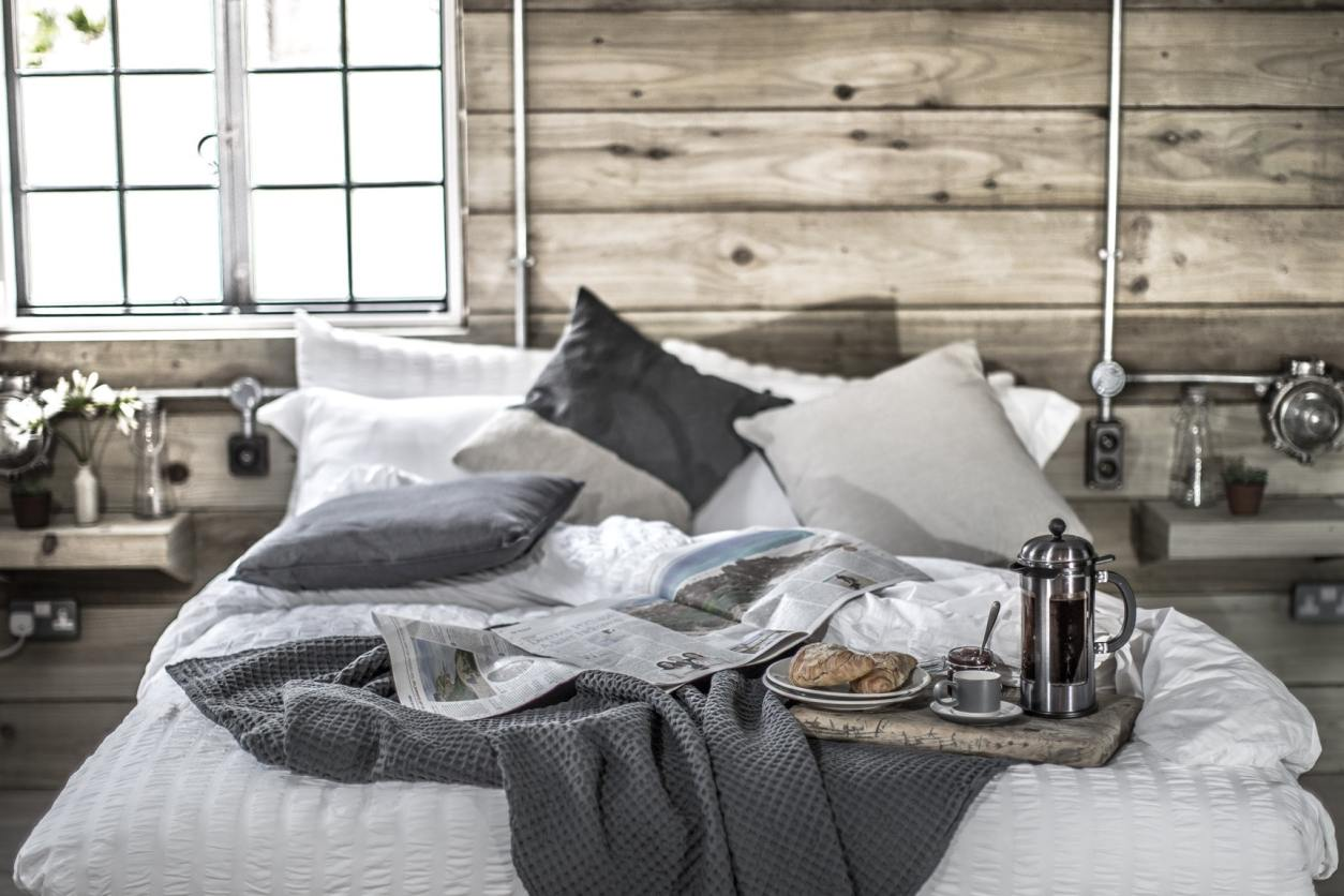 rustic-industrial-bedroom-with-white-and-grey-bedding-in-the-old-fish-cellar-in-mousehole