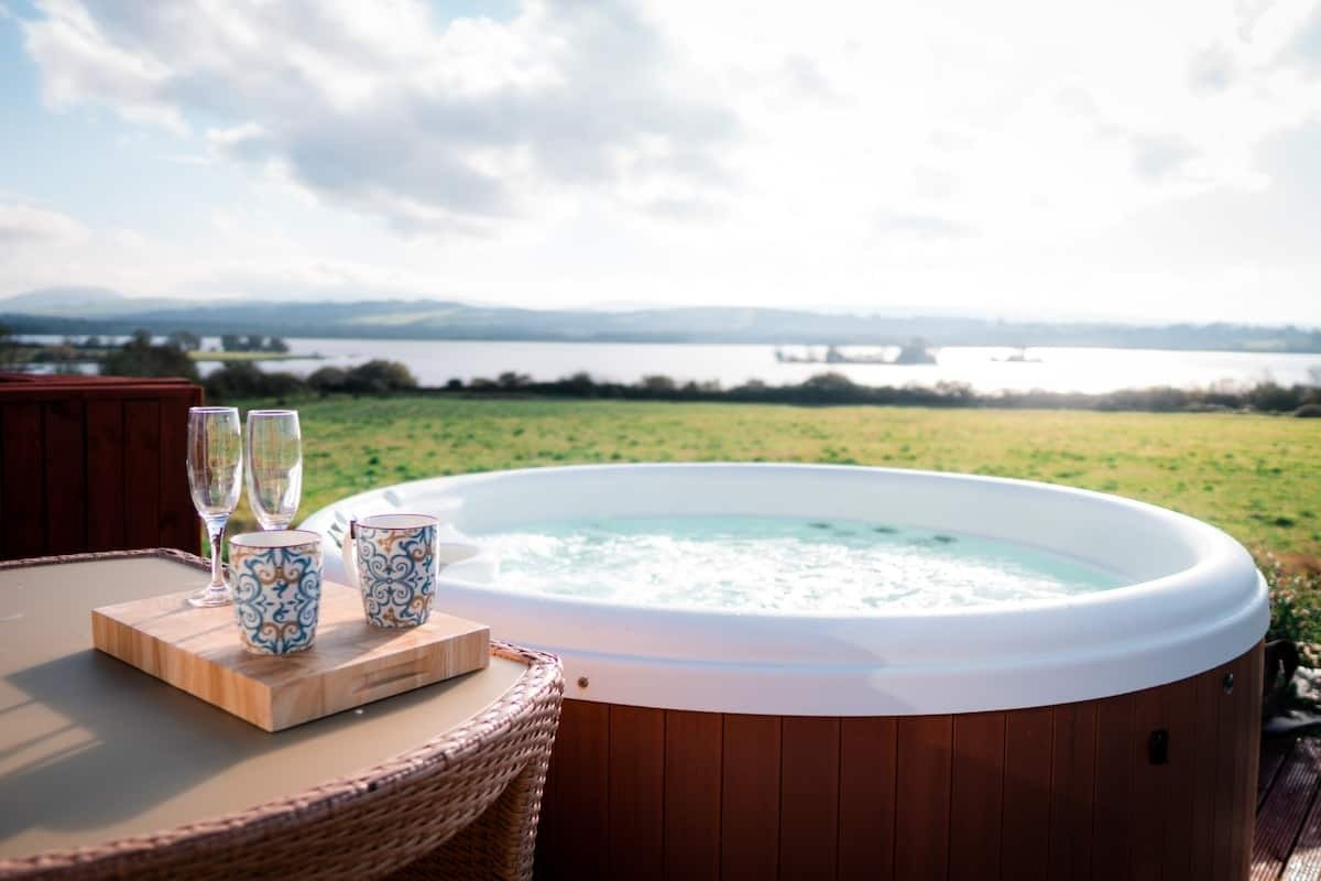 table-and-hot-tub-in-field-with-lake-in-background-at-killaloe-luxury-pod-glamping-with-hot-tub-ireland