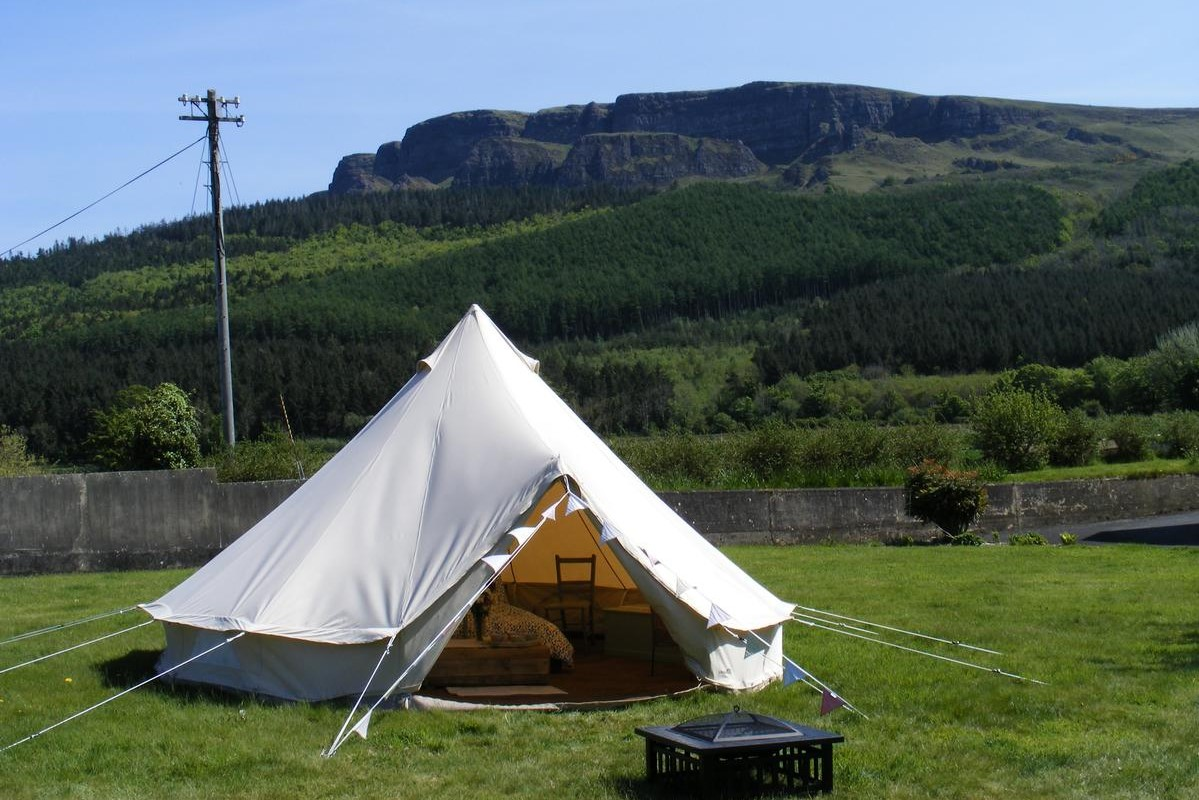 white-bell-tent-in-field-at-swanns-bridge-glamping-with-mountains-in-background