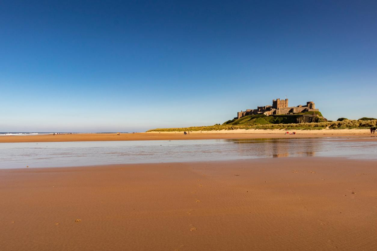 bamburgh-castle-on-hill-out-at-sea-by-sandy-beach-at-sunset-best-places-to-visit-in-northumberland
