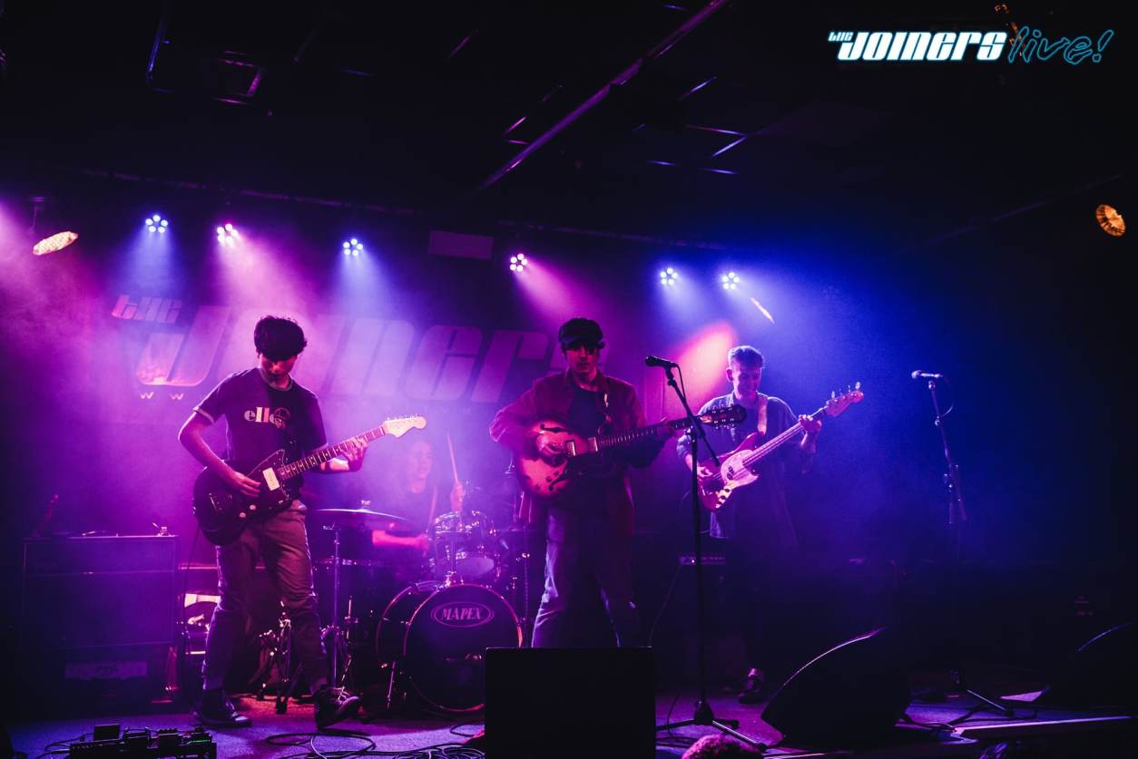 band-on-stage-playing-guitars-lit-up-by-purple-lights-at-the-joiners-southampton