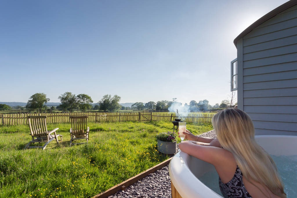 blonde-woman-in-hot-tub-with-glass-of-champagne-overlooking-field-by-grey-goose-shepherds-hut