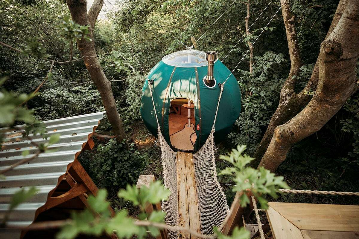 bridge-leading-to-green-round-tree-tent-suspended-in-air-glamping-somerset