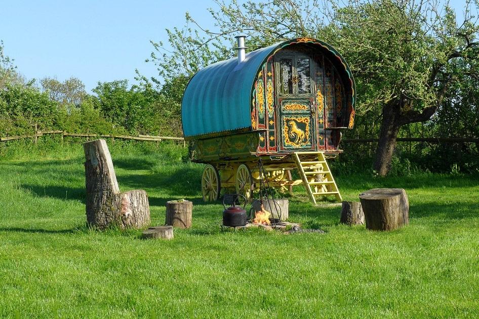 colourful-gypsy-caravan-by-campfire-in-field