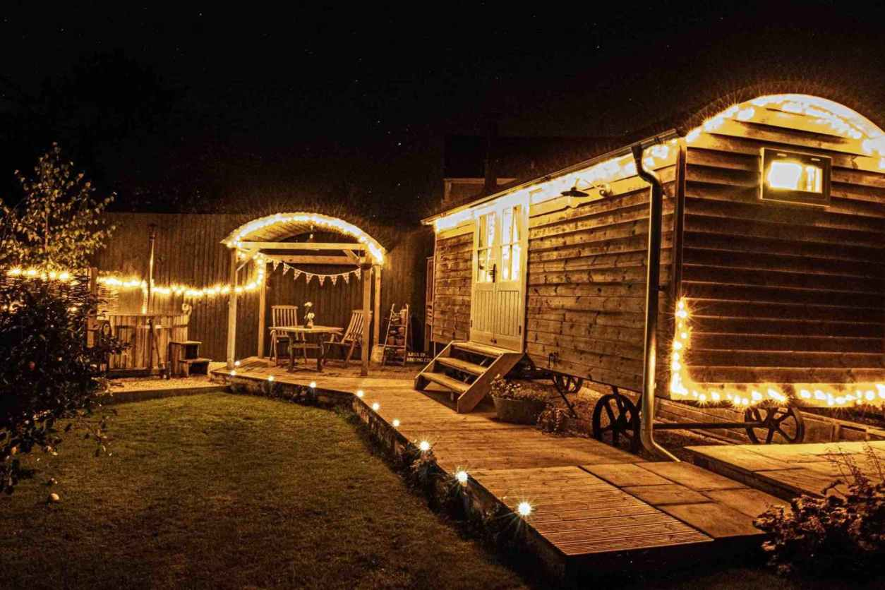 esmes-escape-shepherds-hut-on-decking-lit-up-at-night