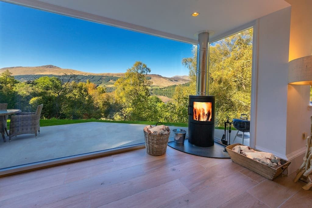 fireplace-in-corner-of-the-tractor-shed-with-glass-walls-and-gardens-overlooking-mountains-lodges-with-hot-tubs-scotland