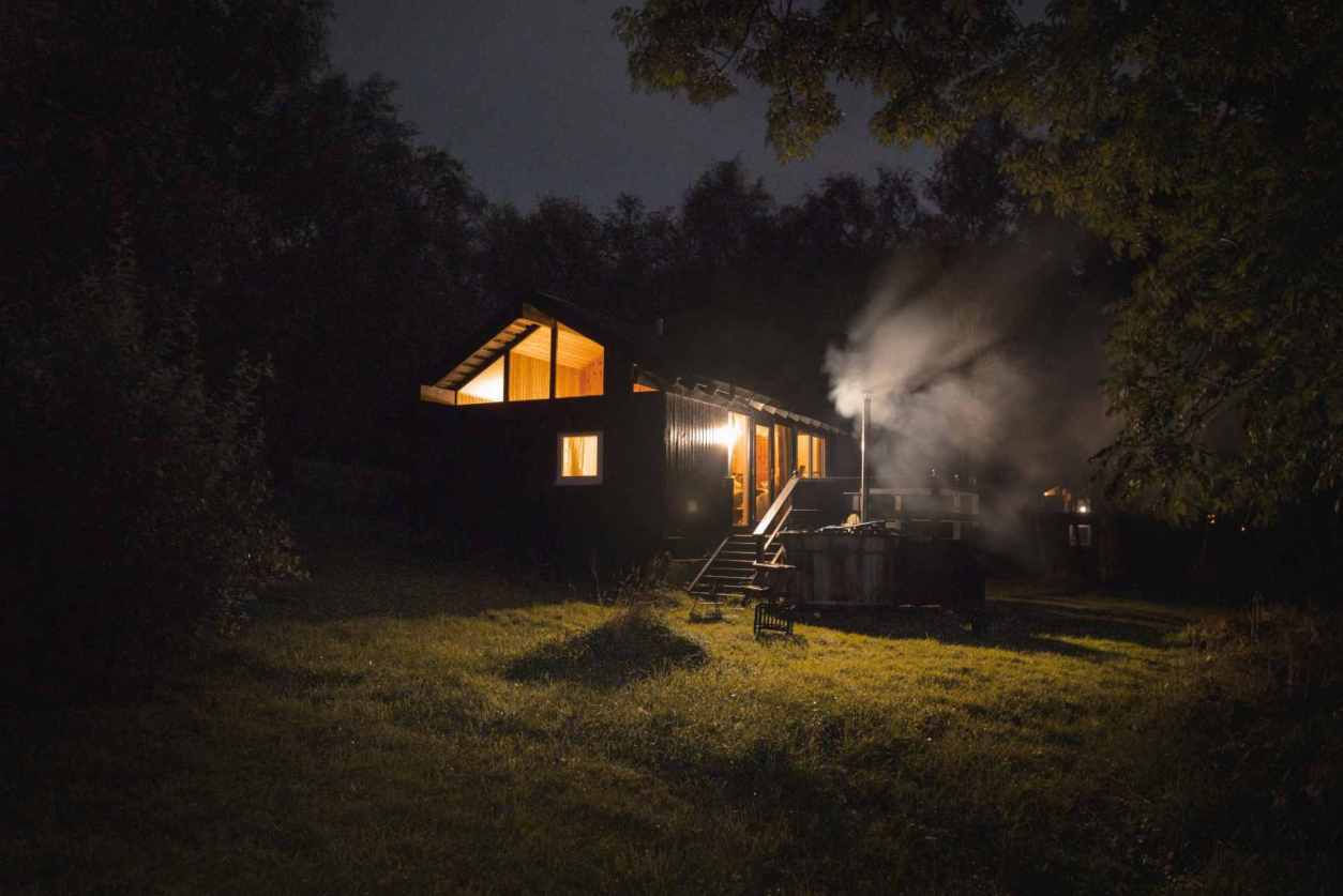 fyne-cabin-with-hot-tub-in-field-lit-up-at-night