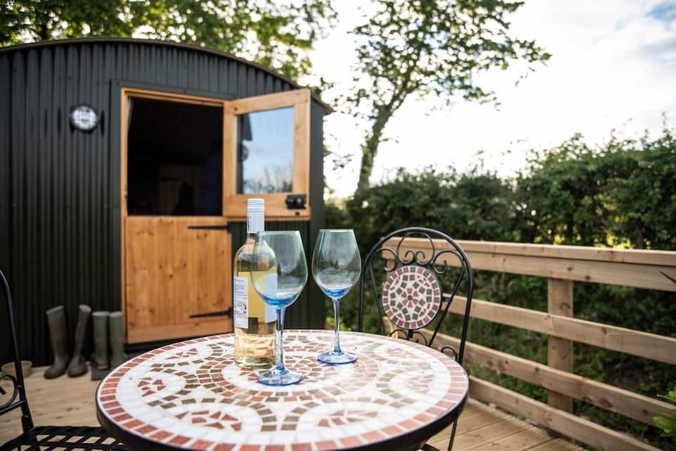 garden-table-with-glasses-of-wine-in-front-of-green-bank-shepherds-hut-in-cockermouth-airbnbs-lake-district