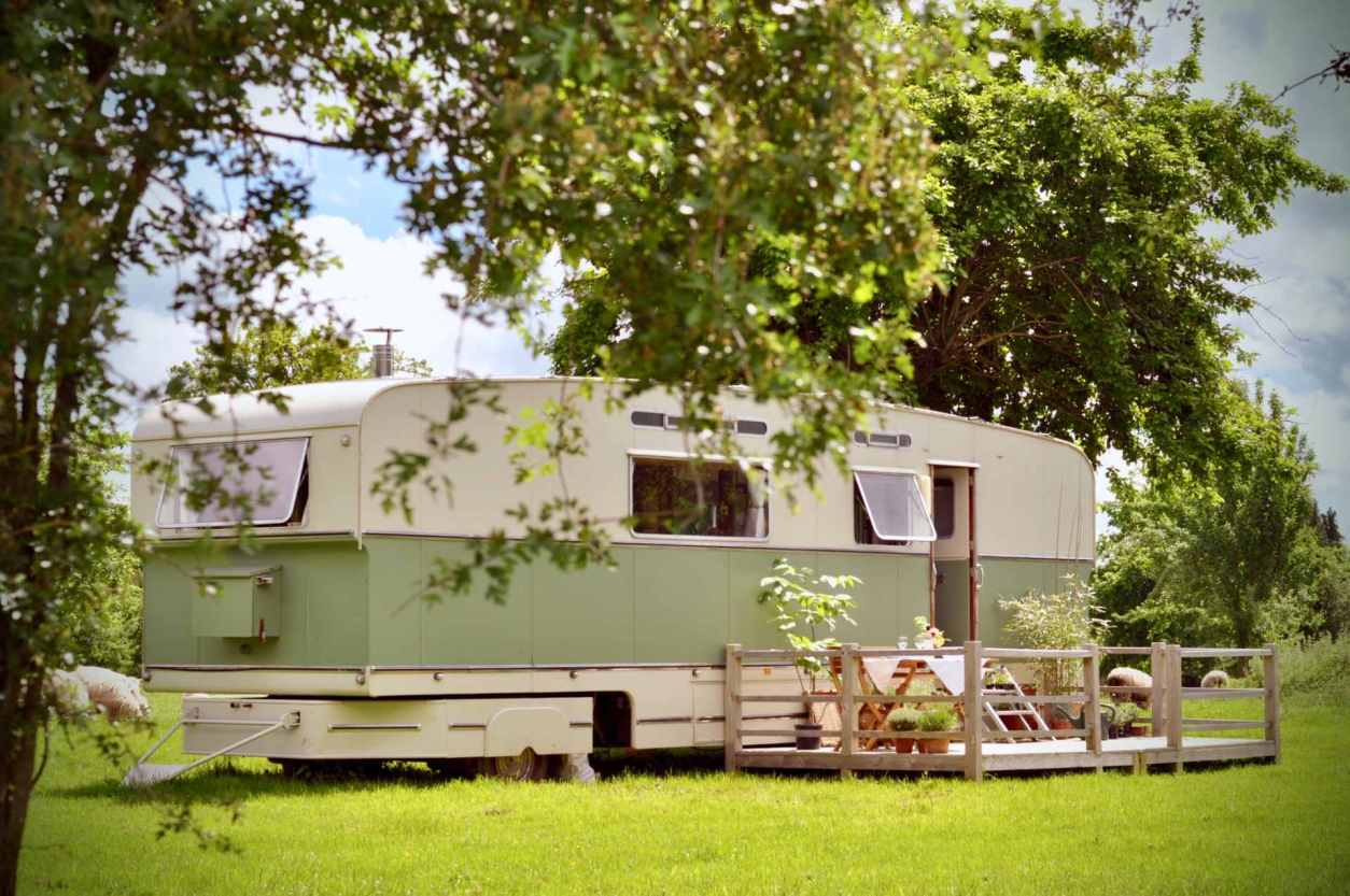 green-and-white-sipson-caravan-with-decking-in-field-on-sunny-day