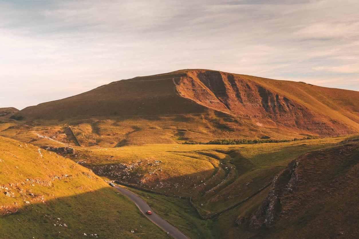 green-mountain-under-cloudy sky-at-sunset-mam-tor-best-peak-district-walks