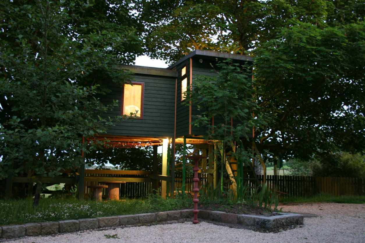 green-swallows-return-treehouse-lit-up-in-the-evening-treehouses-ireland