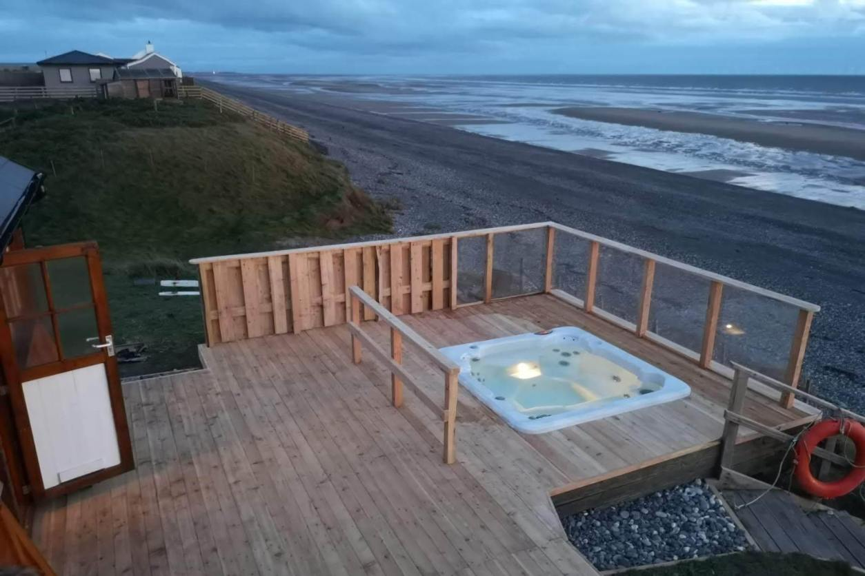 hot-tub-in-decking-of-stone-beach-cabin-at-sunset