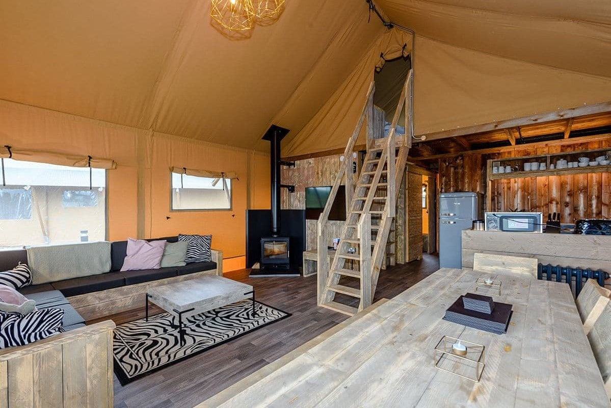 interior-of-safari-tent-with-woodburner-kitchen-and-lounge-area-and-steps-leading-up-to-second-floor-ullswater-heights-safari-tent-airbnbs-lake-district