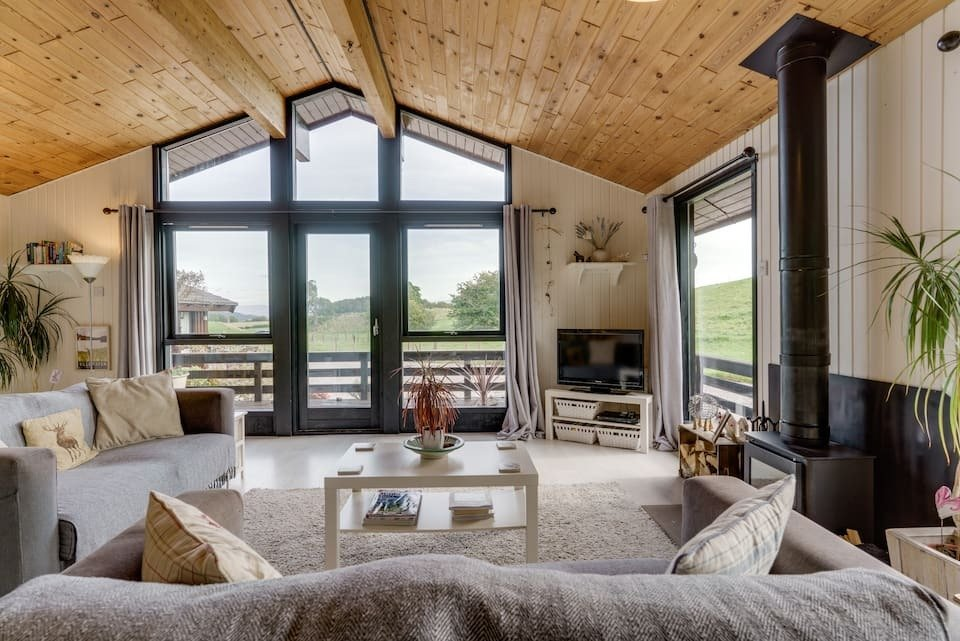living-area-with-fire-and-sofas-and-large-windows-in-herdyview-lodge-in-yanworth-near-ullswater-airbnbs-lake-district