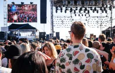 man-in-white-fruit-shirt-and-sunglasses-stood-in-festival-crowd-watching-a-band-in-daytime-packing-list-for-festival