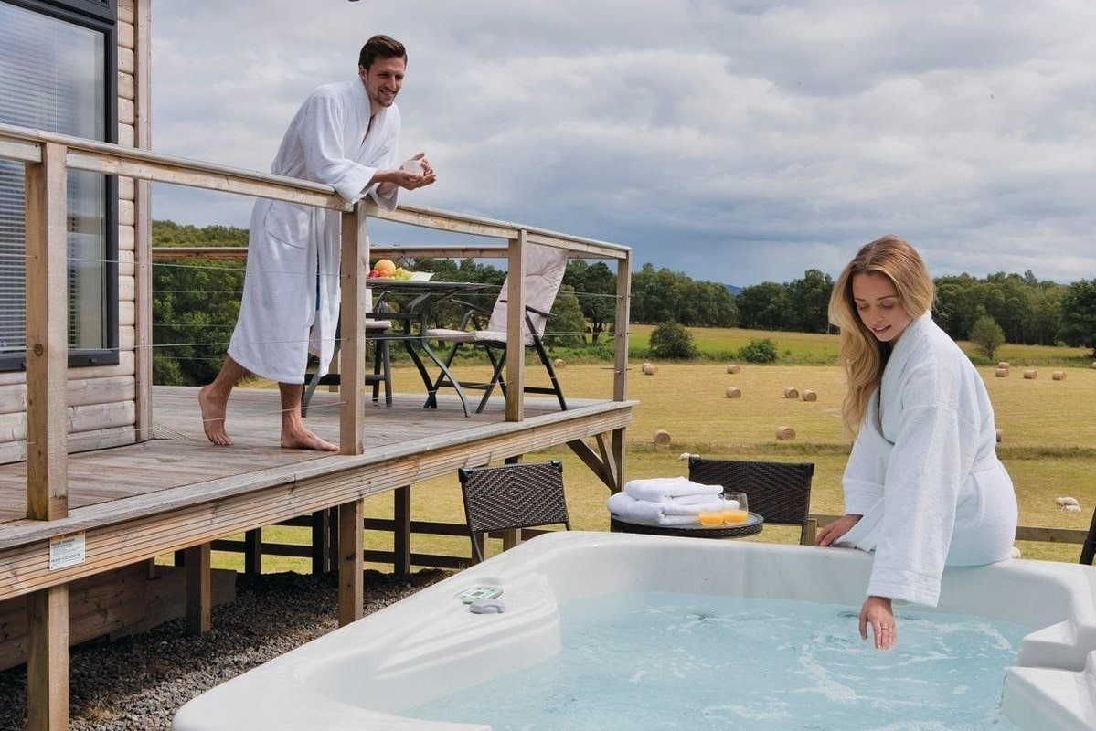 man-on-decking-and-woman-leaning-on-hot-tub-at-kessock-highland-lodges
