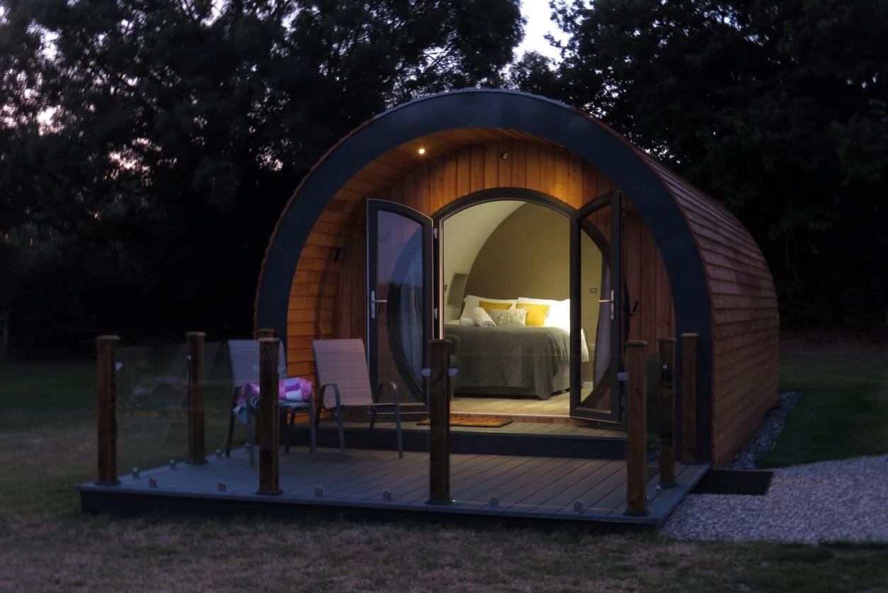 millview-meadow-glamping-pod-lit-up-at-night-in-field