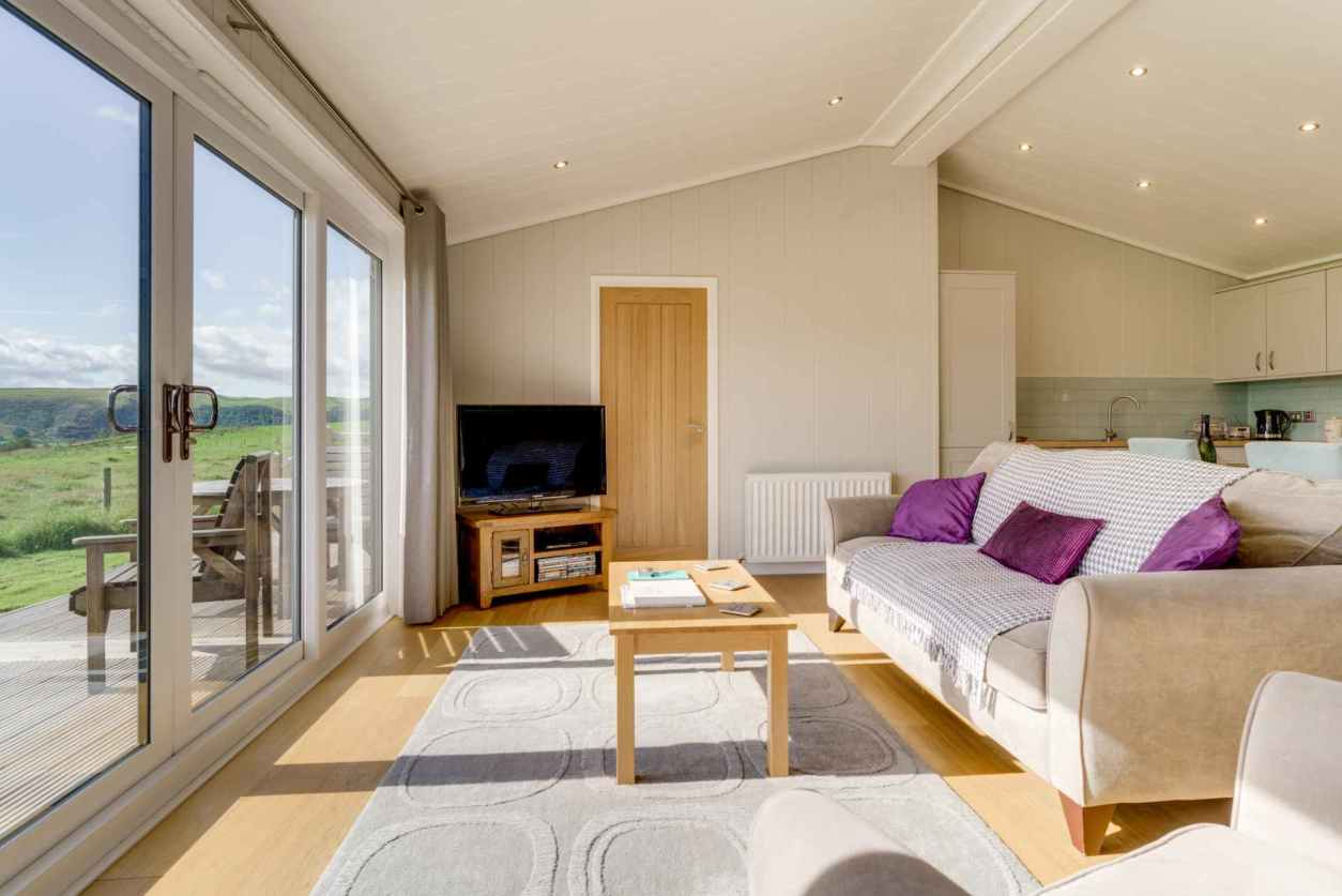 modern-living-area-in-holiday-home-cedar-wood-lodge-with-glass-doors-overlooking-cockermouth-countryside