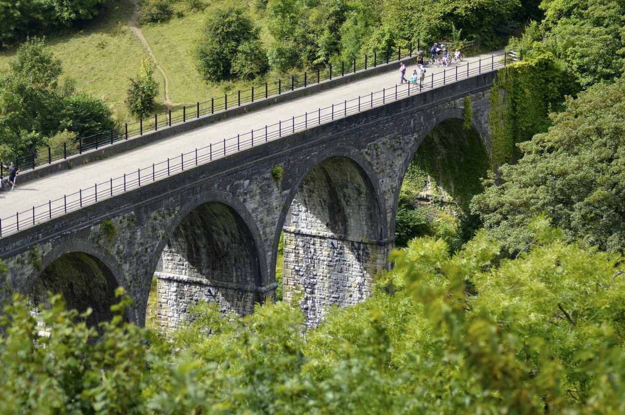 people-walking-over-bridge-viaduct-going-over-green-fields-at-monsal-trail-head