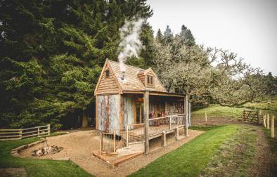 rowan-cabin-at-hesleyside-huts-by-woods-with-smoke-billowing-from-chimney-glamping-northumberland
