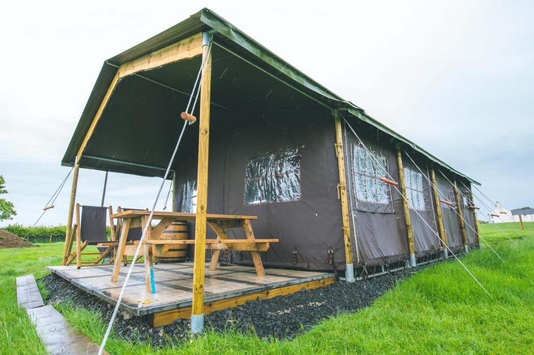 safari-tent-and-decking-in-field-at-feather-down-northumberland-farm-on-rainy-day