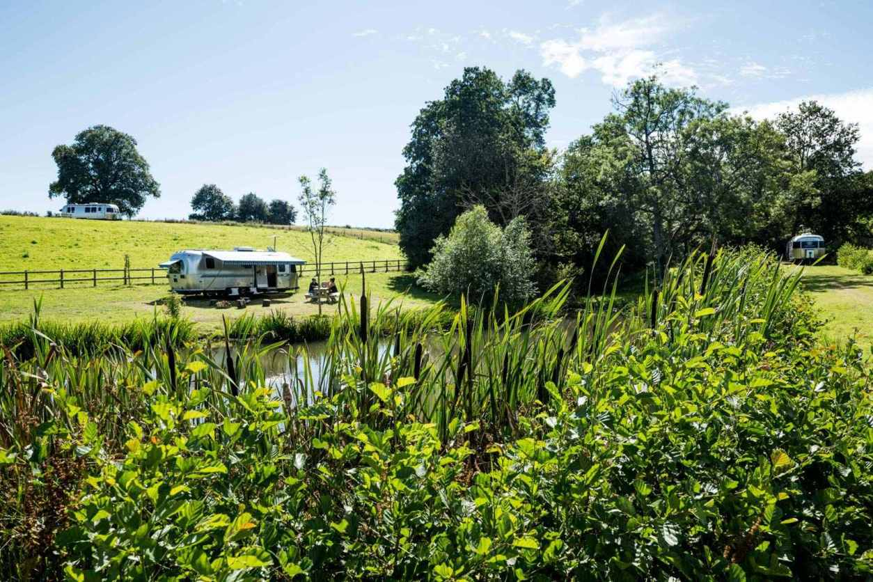 silver-airstream-by-large-lake-on-sunny-day-at-the-wells-glamping-herefordshire