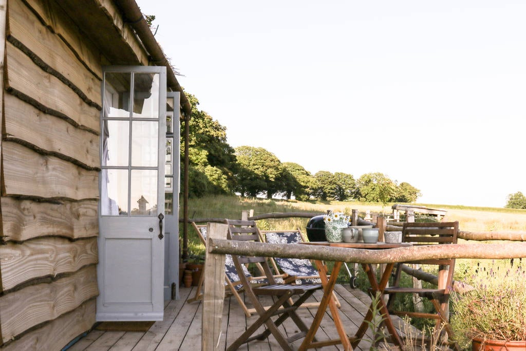 table-and-chairs-on-the-wooden-balcony-outside-of-gardeners-shed-cabin-at-mello-view