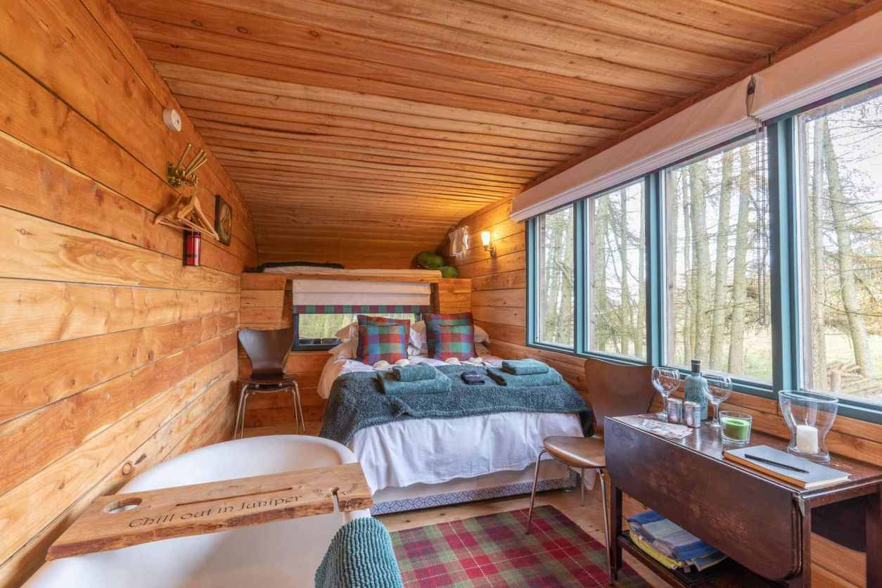 the-inside-of-a-hut-with-a-bed-bath-and-desk-juniper-horsebox-in-perth-and-kinross