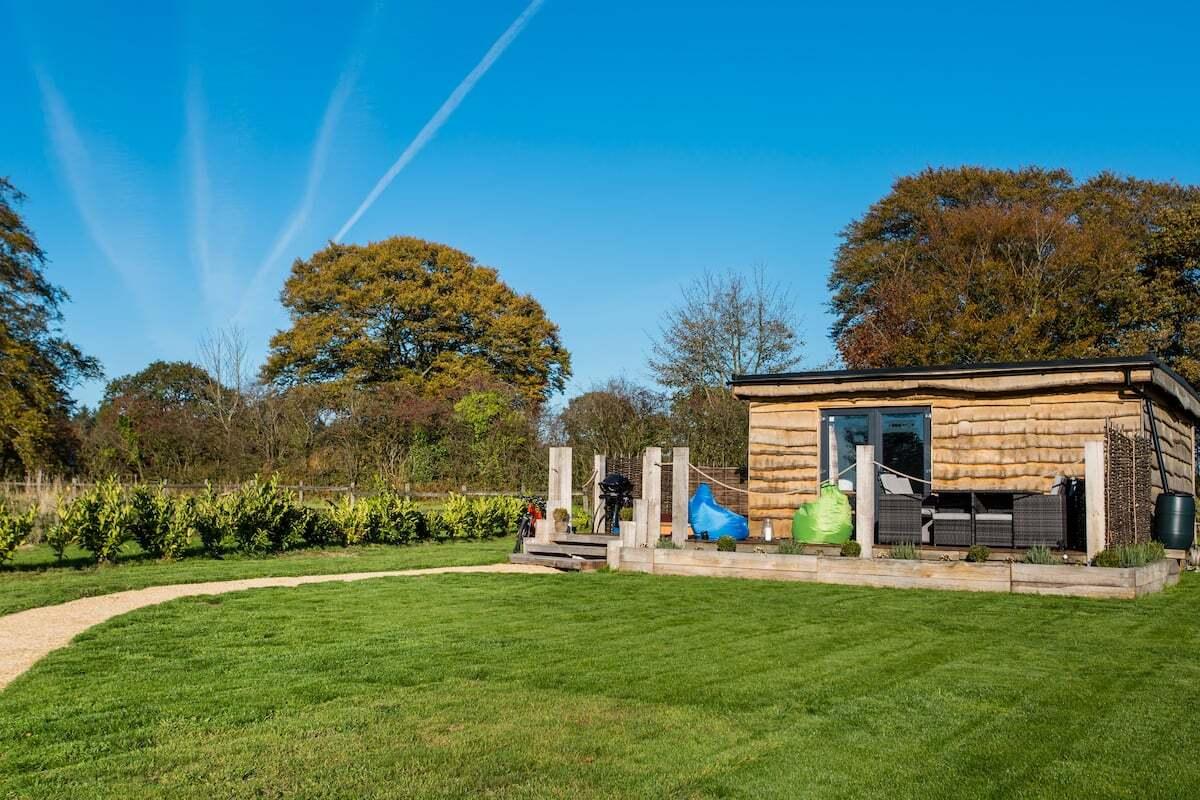 the-oak-escape-cabin-in-field-on-sunny-day