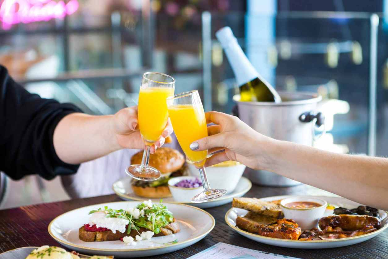 two-hands-cheersing-drinks-over-pitcher-and-piano-bottomless-brunch-southampton