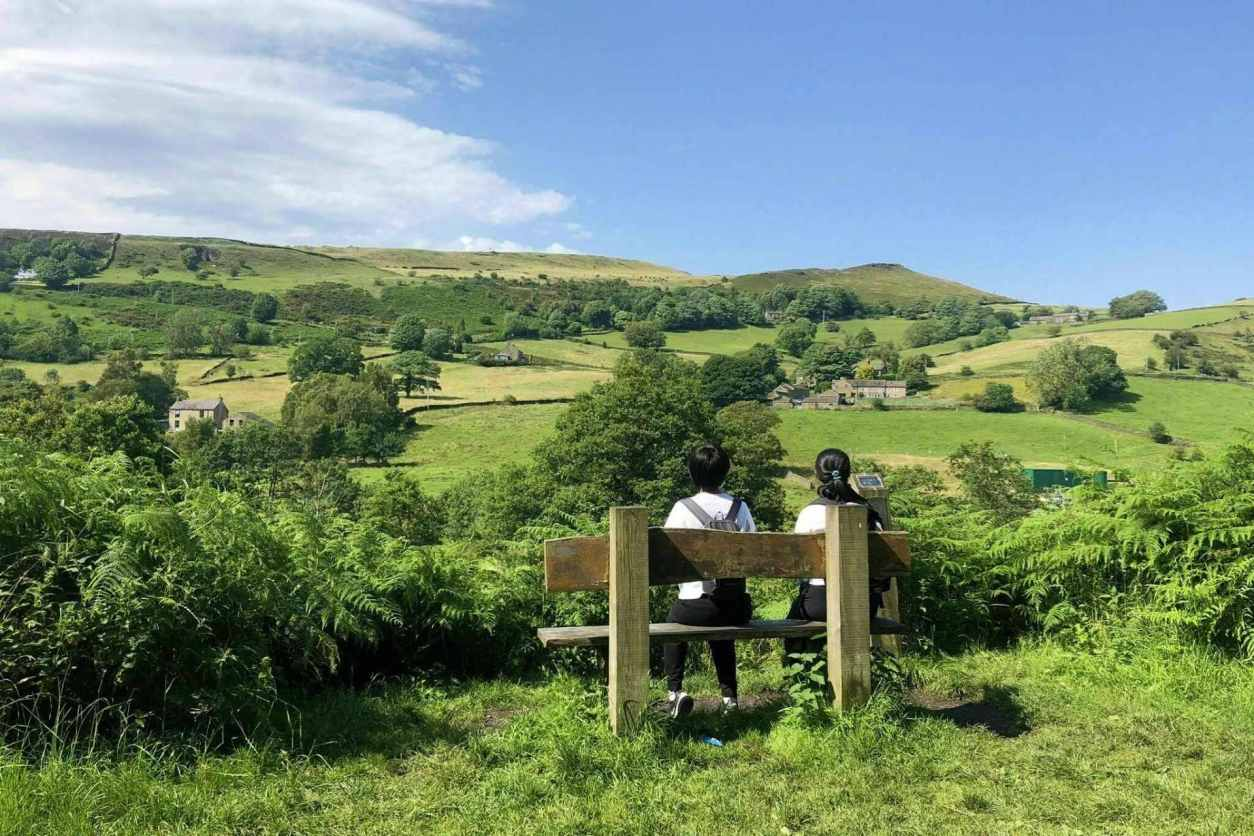 two-people-sat-on-bench-on-sunny-day-overlooking-green-countryside-on-the-sett-valley-trail