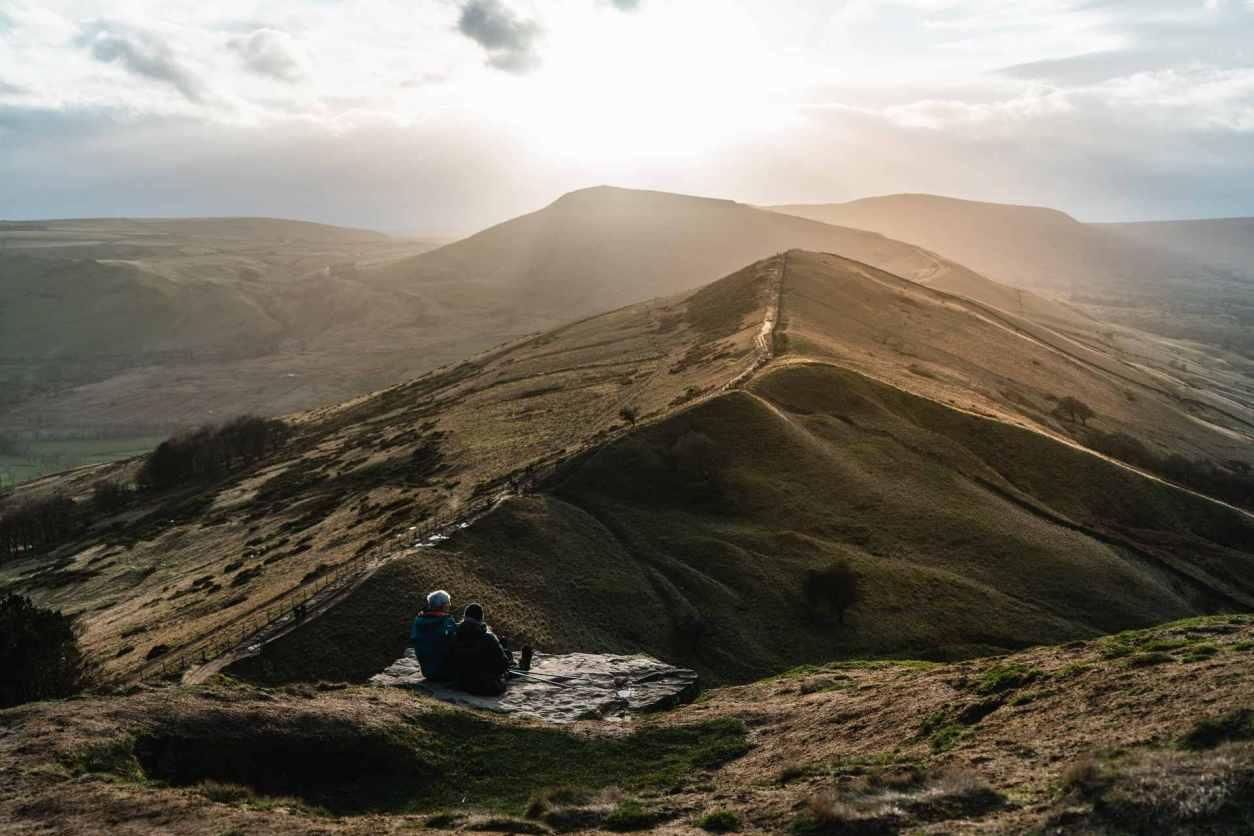 two-people-sat-on-rock-overlooking-mountain-ridge-the-great-ridge-win-hill-and-mam-tor-best-peak-district-walks