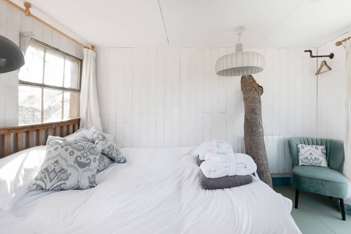 white-bedroom-with-tree-going-through-wall-in-treehouse