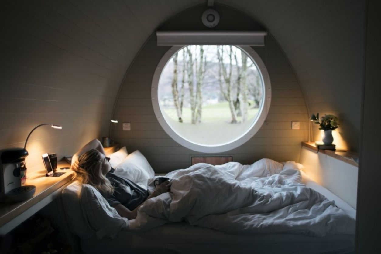 woman-lying-in-bed-in-riverbeds-lodge-glencoe-looking-out-of-a-round-window-lodges-with-hot-tubs-scotland
