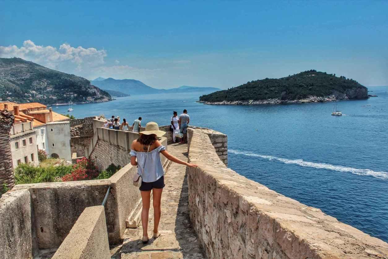 woman-wearing-shorts-and-hat-walking-along-dubvronik-city-walls-by-sea