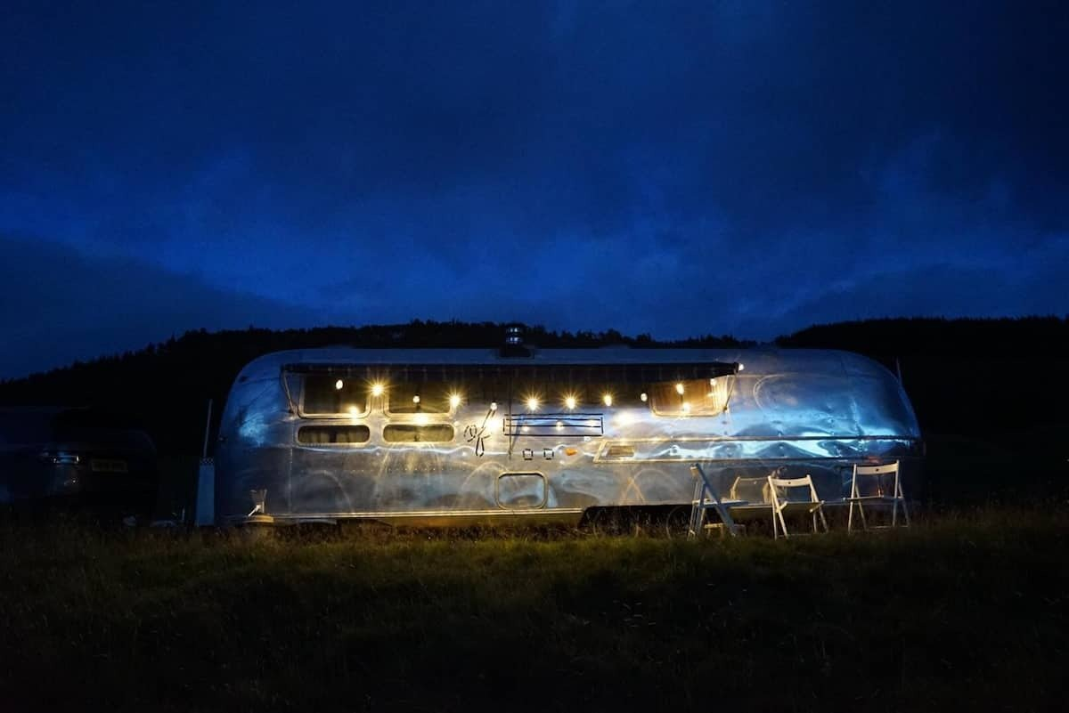 1973-silver-airstream-lit-up-by-fairy-lights-at-night